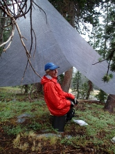 A Room With A View: Karen hanging out under the tarp, hoping the rain will relent so she can hang a hammock under it.